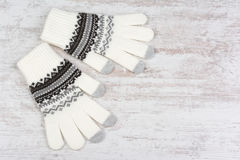 Ett par av vintern stack handskar på vit träbakgrund Arkivfoto