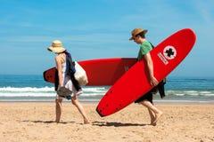 Ett par bär surfingbrädor på stranden av Cordoama Royaltyfria Foton