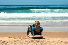 Ett par bär surfingbrädor på stranden av Cordoama royaltyfri foto