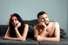 Ett par, en man och en kvinna ligger i säng utan sexuell lust, apati, förälskelse är över Förspelet i säng, brist av könsbestämme royaltyfria bilder