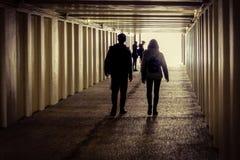 Ett par går i gångtunnelen med en grupp av flickor på ingången royaltyfri bild