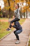 Ett par gör sportar i en höst parkerar Grabben huka sig ned rymma flickan på hans skuldror Arkivbilder