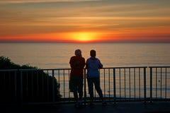 Ett par hänger ut på räcket som håller ögonen på solen att ställa in arkivbild