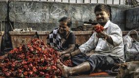 Ett par i gatan av bombay med lotten av rosor royaltyfria bilder