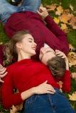 Ett par ligger på grönt gräs i gula lönnlöv, deras framsidor är nästan, ett datum, vänner, ett gift par, royaltyfria bilder