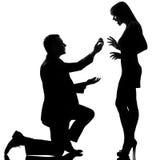 Ett par man den erbjudande förlovningsringen och kvinnan den lyckliga överraskningen Arkivbild