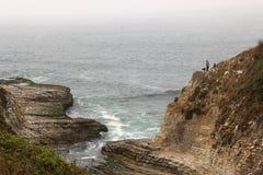 Ett par och deras hund fotvandrar klippor nära Davenport, CA av huvudväg 1 Arkivbilder