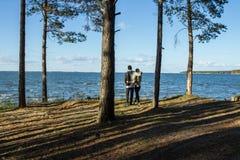 Ett par på sjön, på solnedgången, i en pinjeskog Royaltyfria Bilder
