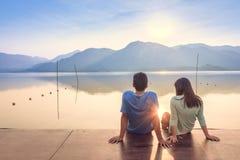 Ett par på träporten på en sjö på solnedgång royaltyfri fotografi