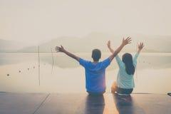 Ett par på träporten på en sjö på solnedgång Arkivfoto