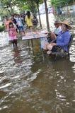 Ett par säljer lottsedlar i en översvämmad gata av Bangkok, Thailand, på 31 Oktober 2011 Arkivbilder