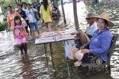 Ett par säljer lottsedlar i en översvämmad gata av Bangkok, Thailand, på 31 Oktober 2011 arkivbild