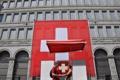 Ett par som är förälskat framme av den enorma schweiziska flaggan på thamedborgaren fotografering för bildbyråer
