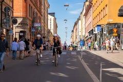 Ett par som cyklar på en fot- stadsshoppinggata Arkivbilder