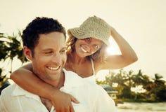 Ett par som kopplar av på strandbegreppet arkivbilder