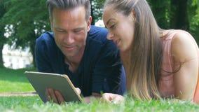 Ett par som kyler i parkera, de hållande ögonen på fotona på deras minnestavla och postar på sociala nätverk stock video