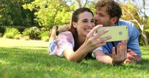 Ett par som ligger på gräset som tar en selfie lager videofilmer