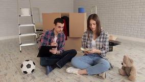 Ett par som räknar pengar och ner skriver deras kostnader i notepad inflyttningsfest lager videofilmer