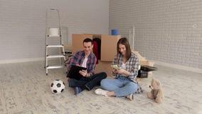 Ett par som räknar pengar och ner skriver deras kostnader i notepad inflyttningsfest arkivfilmer
