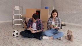Ett par som räknar pengar och ner skriver deras kostnader i notepad inflyttningsfest stock video