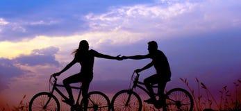 Ett par som rider cyklar och rymmer handen arkivfoto
