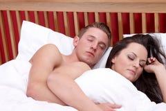 Ett par som sover i säng Fotografering för Bildbyråer