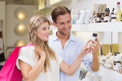 Ett par som testar en prövkopia av skönhetsprodukter Royaltyfri Bild