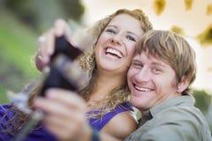 Ett par som tycker om ett exponeringsglas av Wine i parken Royaltyfria Foton
