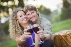 Ett par som tycker om ett exponeringsglas av Wine i parken Arkivfoto