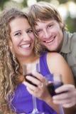 Ett par som tycker om ett exponeringsglas av Wine i parken royaltyfri fotografi