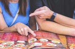 Ett par som utarbetar den utländska menyn royaltyfri bild