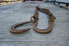 Ett par stålsätter krokar som lägger på baksidan av en säng av en bärgningsbil arkivfoton