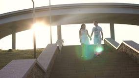 Ett par stiger ned momenten i parkera på solnedgången arkivfilmer