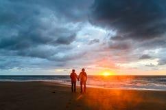 Ett par under solnedgången på stranden Arkivfoto