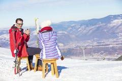 Ett par vilar på vardagsrum i picknickzon på europé skidar semesterorten Royaltyfri Fotografi