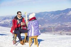 Ett par vilar på vardagsrum i picknickzon på europé skidar semesterorten Fotografering för Bildbyråer