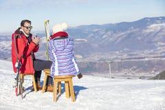 Ett par vilar på vardagsrum i picknickzon på europé skidar semesterorten Royaltyfri Bild