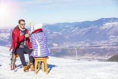Ett par vilar på vardagsrum i picknickzon på europé skidar semesterorten Royaltyfria Bilder