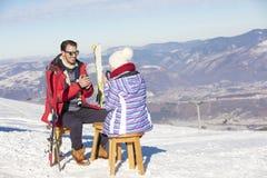 Ett par vilar på vardagsrum i picknickzon på europé skidar semesterorten Royaltyfria Foton