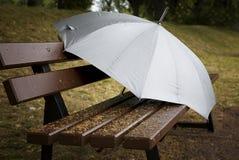 Ett paraply från regnet på parkerar bänken, makro royaltyfri foto