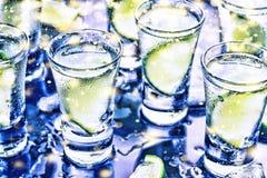 Ett parti i klubban Coctailar på stången _ Vodka, gin, tequila med is och limefrukt Alkoholiserad coctailcoctail selektivt royaltyfri foto