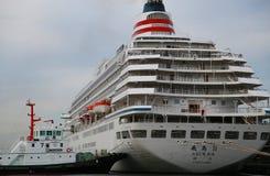 Ett passagerareskepp och en bogserbåt av Yokohama port Royaltyfri Foto
