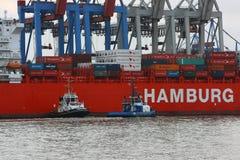 Ett patrullfartyg och en towboat fungerar bredvid lastfartyget av den tyska `en för den sändningsföretags`-Hamburg suden, Arkivfoto