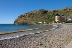 Ett Pebble Beach och en sikt till det Dom Pedro Baia hotellet i ön av madeiran Arkivfoto