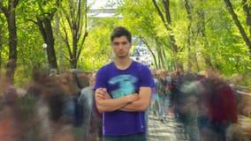 Ett personanseende outcropped i folkmassa av folk, på bakgrundsgräsplanträd Tid schackningsperiod stock video