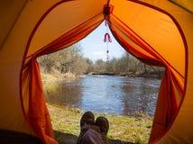 Ett personsammanträde i ett orange tält, läger i banken av floden i vår Fot selfie av handelsresanden Avkopplad färgrik blick arkivfoto