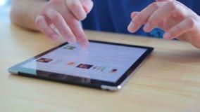 Ett personsammanträde på tabellen och använda en touchpad arkivfilmer