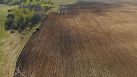 Ett pittoreskt jordbruks- fält med mörkt fertilt land och engenomdränkt traktor av röd färg som plogar arkivfilmer