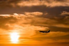 Ett plant flyg på den härliga solnedgången Royaltyfria Foton