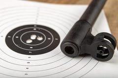 Ett pneumatiskt vapen på en trätabell på en skjutbana Skyttetillbehören behövde för att skjuta sportar arkivbild